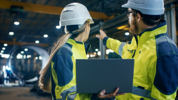 à l'intérieur de la lourde usine industrielle femme ingénieur industriel contient ordinateur portable et a des discussions avec le chef de projet. dur, ils portent chapeaux et vestes de sécurité. dans la soudure de fond / ferronnerie en cours. - chef de projet photos et images de collection