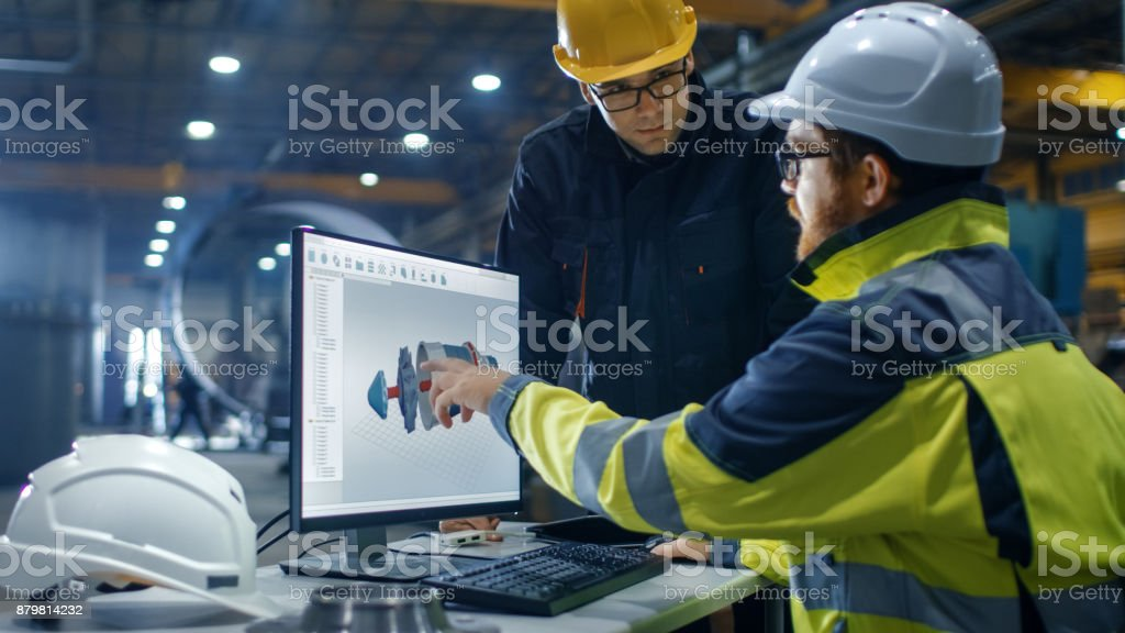 Inside the Heavy Industry Engineer Works on the Personal Computer while Talking with the Project Manager. He Designs Turbine/ Engine in  3D CAD Program. stock photo