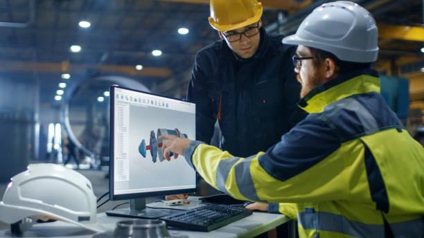 im inneren arbeitet der schwerindustrie-ingenieur auf dem pc beim reden mit dem projektleiter. er entwirft turbine / motor in 3d cad-programm. - projektmanager stock-fotos und bilder
