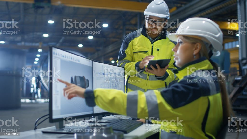Inside the Heavy Industry Factory Female Industrial Engineer Works on Personal Computer She Designs 3D Turbine Model, Her Male Colleague Talks with Her and Uses Tablet Computer. stock photo