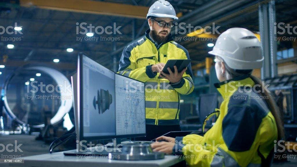 In der Schwerindustrie Fabrik arbeitet weibliche Wirtschaftsingenieur auf Personal Computer sie Designs 3D Turbine Modell, ihr männlicher Kollege spricht mit ihr und Tablet-Computer verwendet. – Foto