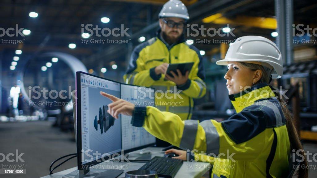In der Schwerindustrie Fabrik arbeitet weibliche Wirtschaftsingenieur auf Personal Computer sie Designs 3D-Engine Modell, ihr männlicher Kollege spricht mit ihr und Tablet-Computer verwendet. Niedrigen Winkel Aufnahmen. – Foto