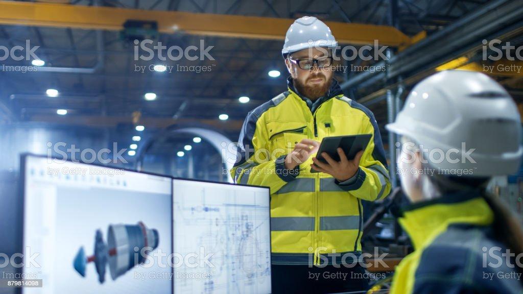 In der Schwerindustrie Fabrik arbeitet weibliche Wirtschaftsingenieur auf Personal Computer sie Designs 3D-Engine Modell, ihr männlicher Kollege spricht mit ihr und Tablet-Computer verwendet. – Foto