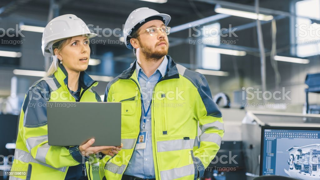 Inside the Manufacturing Factory Male Mechanical Engineer Works on...