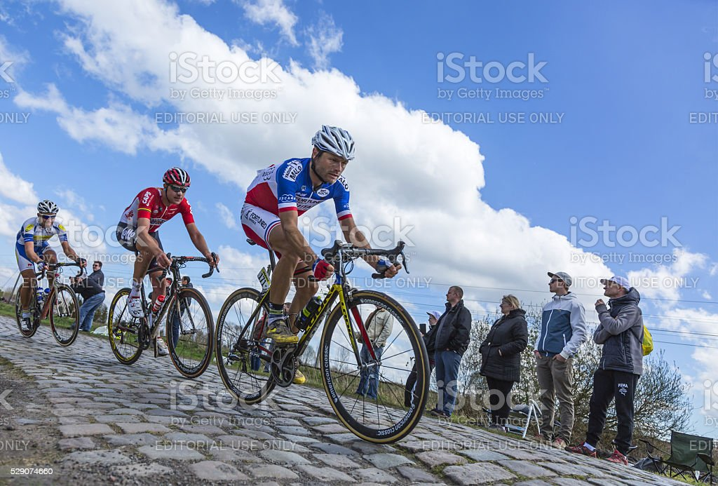 Inside the Peloton - Paris Roubaix 2016 Hornaing ,France - April 10,2016: Group of three cyclists riding in the peloton on a paved road in Hornaing, France during Paris Roubaix on 10 April 2016. 2016 Stock Photo