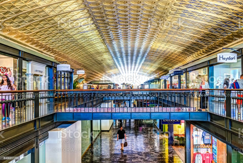 Inside Union Station in capital city with shopping mall and arched ceiling by stores stock photo