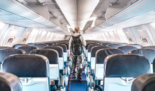 Inside view of commercial airplane with lonely man traveler - Emergency travel concept about flight cancellation - Aerospace industry crisis with empty plane on bright azure filter stock photo