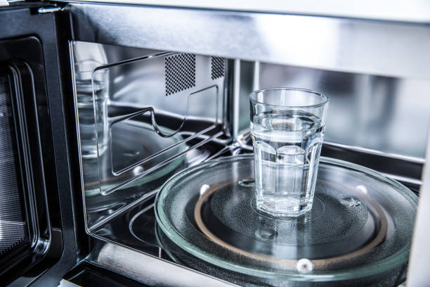 Innenansicht des neuen sauberen staniless Mikrowellenherds mit einer Tasse reinem Wasser – Foto