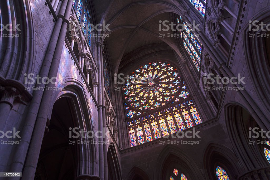 Stained glass and arches inside this purpled colored light church