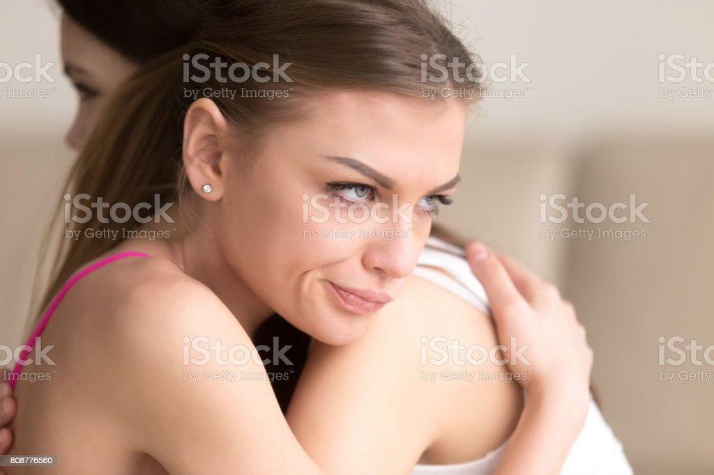 Insincere female hiding her envy when hugs friend stock photo