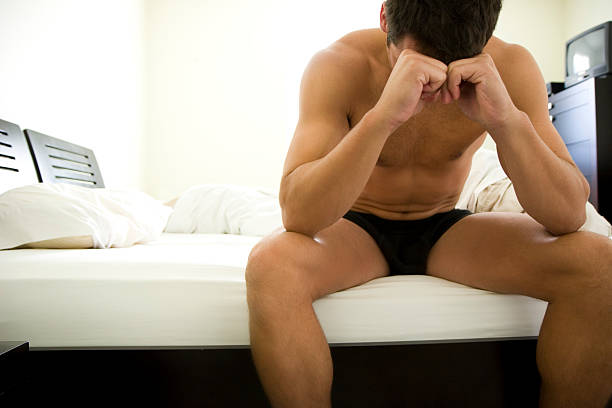 Insomnia Man sitting at the edge of bed. sexually transmitted disease stock pictures, royalty-free photos & images