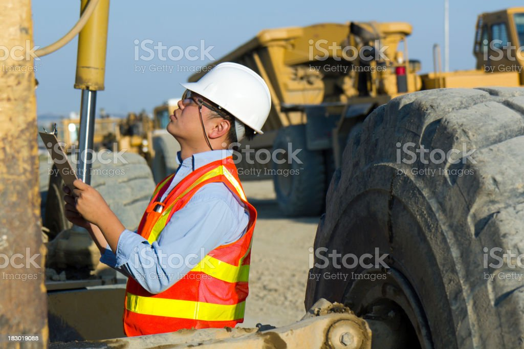 Inspecting a Construction Machine royalty-free stock photo