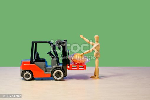 Wooden doll, toy red forklift, green background,