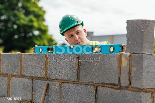 A shot of a spirit level being used to check some brickwork by a caucasian male construction worker.