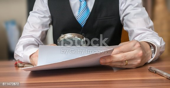 istock Inspection of document with magnifying glass. Layer is analysing contract 511472872