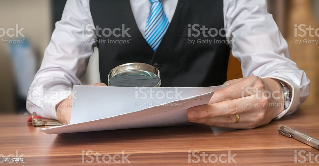 Inspection of document with magnifying glass. Layer is analysing contract stock photo