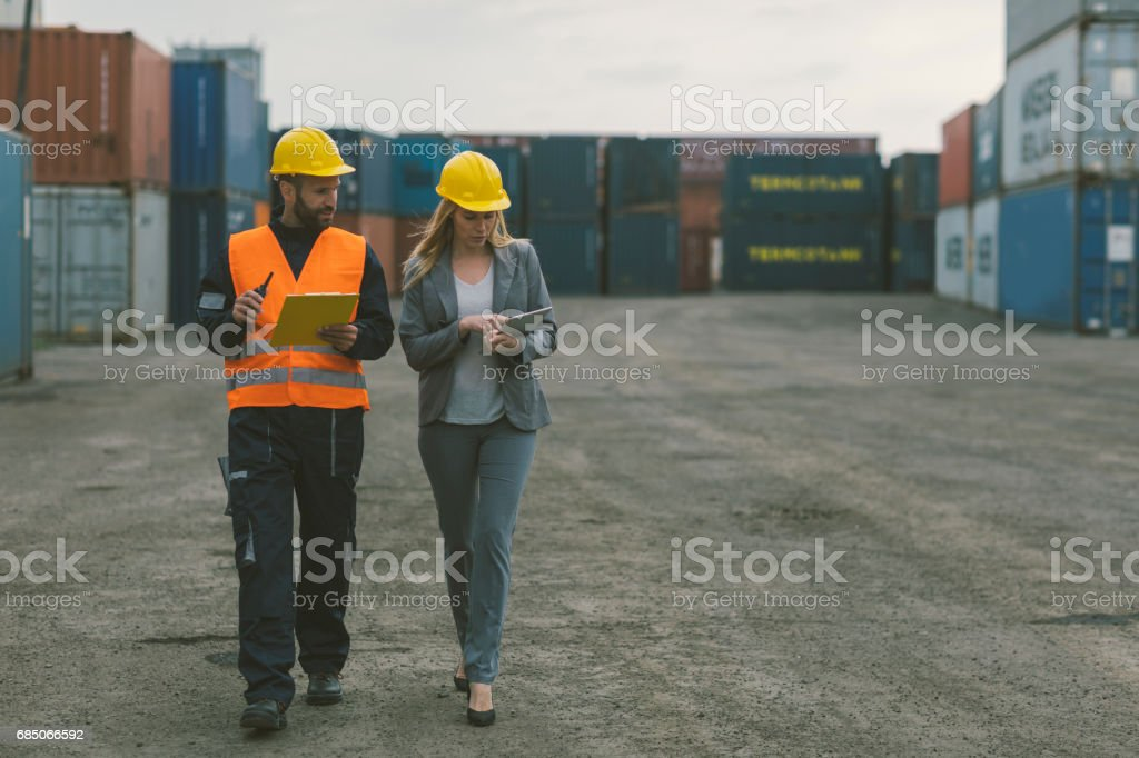 Inspector and manual worker checking cargo containers royalty-free stock photo