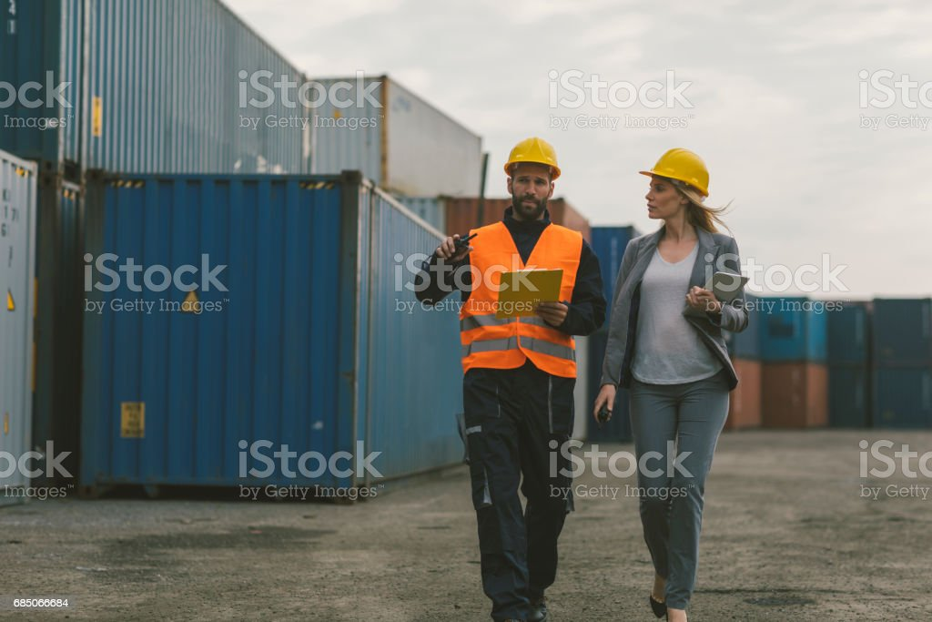 Inspector and manual worker checking cargo containers stock photo
