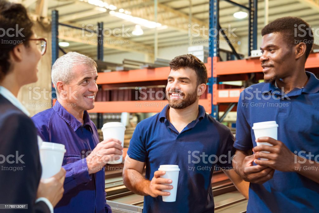 Inspector and workers discussing at coffee break Female inspector and workers discussing while having coffee in industry. Expertise are taking break in warehouse. They are related to manufacturing occupation. 20-24 Years Stock Photo