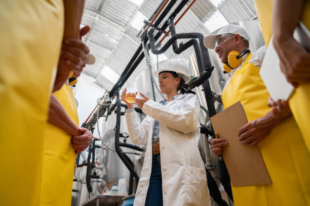 ispettore che fa il controllo qualità su un campione di birra in un birrificio - campione scientifico foto e immagini stock