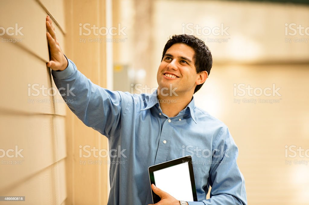 Inspector, engineer examines building wall, window outdoors.  Digital tablet. stock photo
