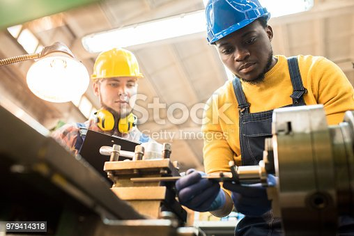 istock Inspector evaluating work of repairing engineer at plant 979414318