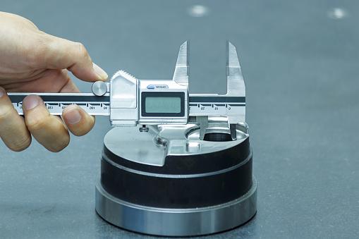 istock Inspector Measuring parts by Vernier Caliper 520096918