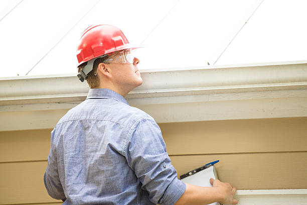 Inspector or blue collar worker examines building roof.  Outdoors. stock photo