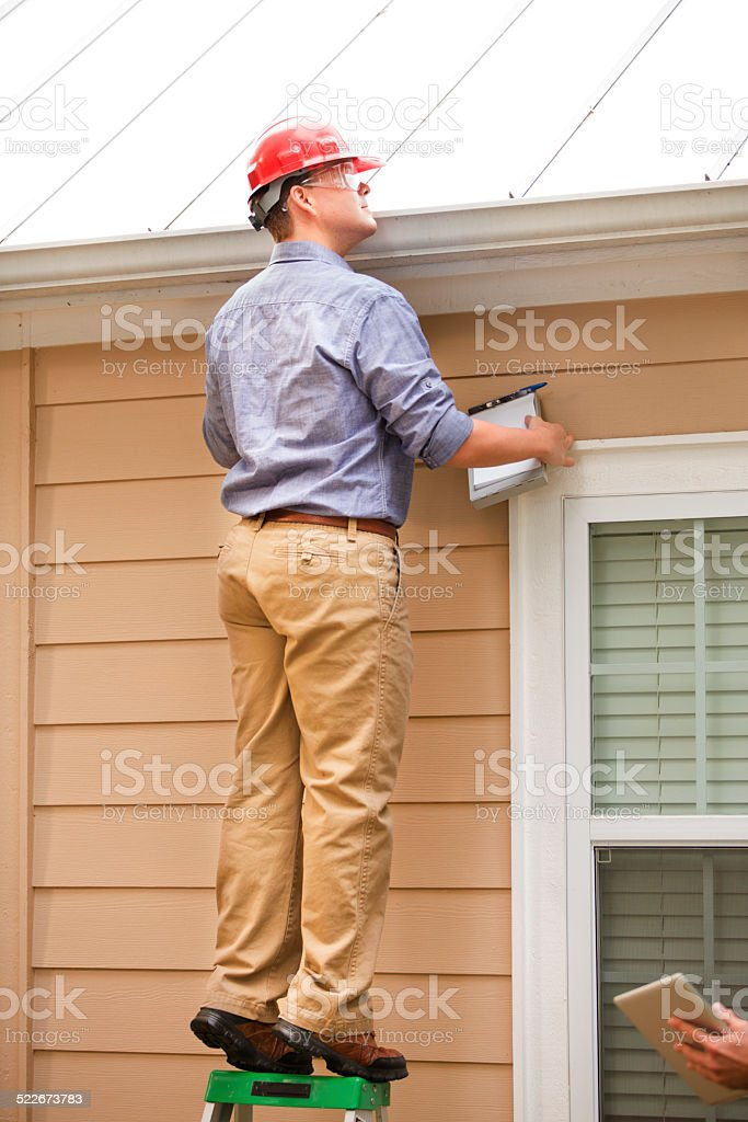 Inspector or blue collar worker examines building roof outdoors. stock photo