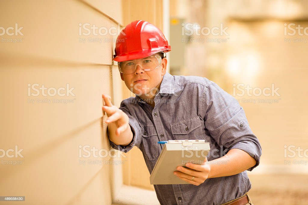 Inspector or blue collar worker examines building wall outdoors. stock photo