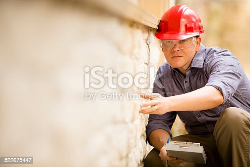 Repairman, building inspector, exterminator, engineer, insurance adjuster, or other blue collar worker examines a building/home exterior wall.  He wears a red hard hat and clear safety glasses and holds a clipboard.