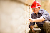 istock Inspector or blue collar worker examines building wall outdoors. 522675447