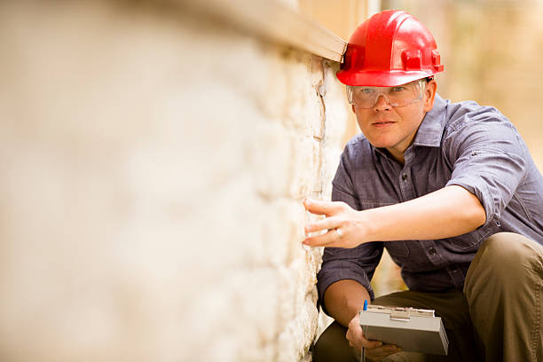 inspector or blue collar worker examines building wall outdoors. - quality control stock photos and pictures