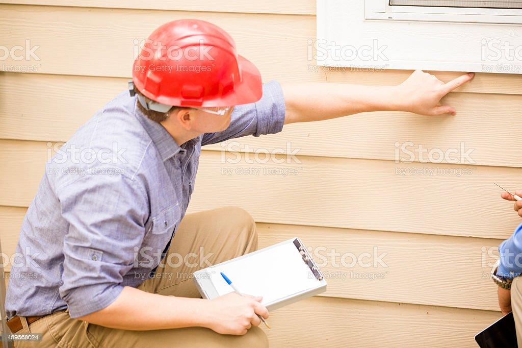 Inspector o azul empleados administrativos examina la construcción de pared, ventana. Al aire libre. - foto de stock