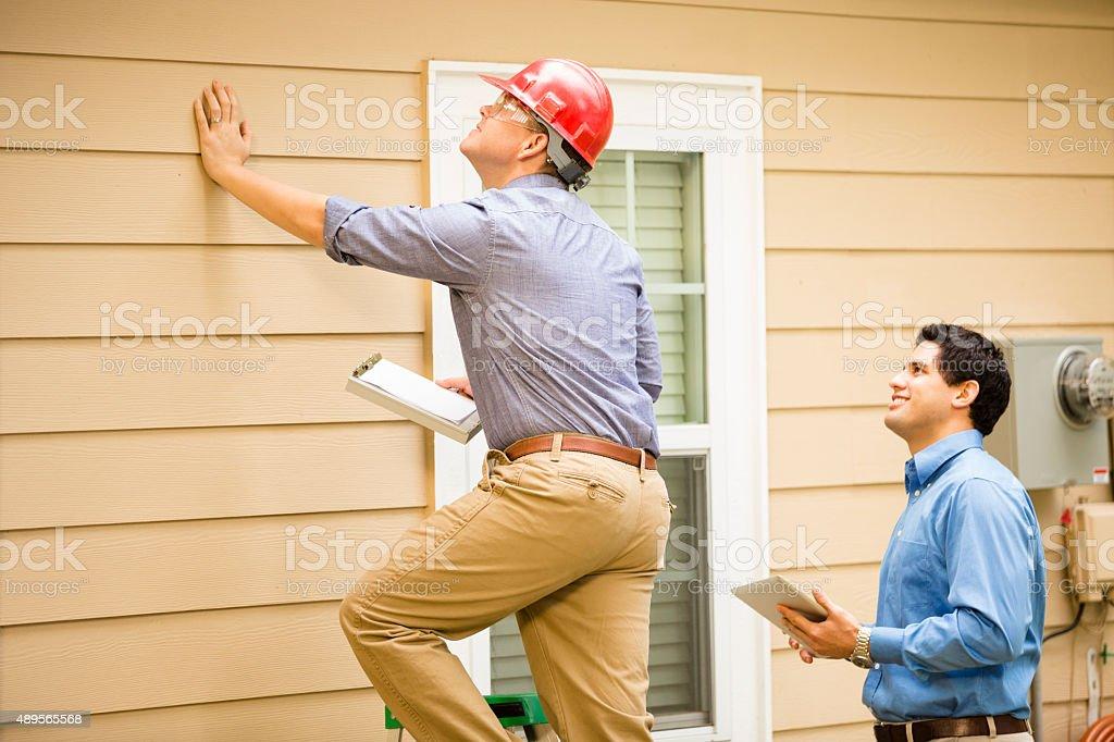 Inspectores o azul empleados administrativos examinar la construcción de pared, base.  Al aire libre. - foto de stock