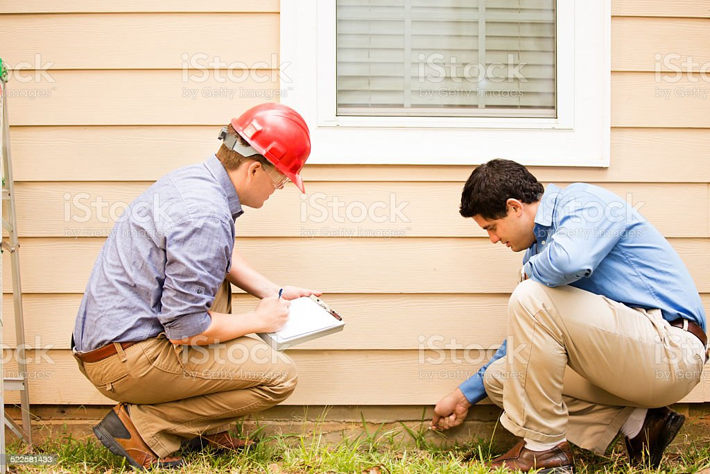 Inspektoren oder blauen Kragen Arbeitnehmer prüfen Gebäude Wand, foundation.  Im Freien. – Foto