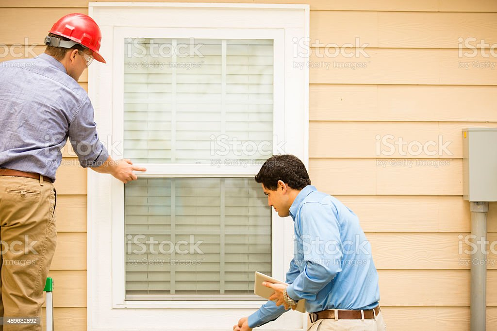 Inspectors or blue collar workers examine building wall, window. Outdoors. stock photo