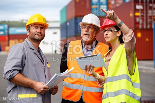 This is a photo of a team of people standing outdoors at a commercial dock. The team  consists of a manual worker, wearing a grey working coat and yellow helmet, holding  some papers, a bussineswoman (engineer), wearing a reflective clothes, holding a digital  tablet and explaining something to a senior man, wearing reflective vest and white  hardhat, who seems to be an investor.
