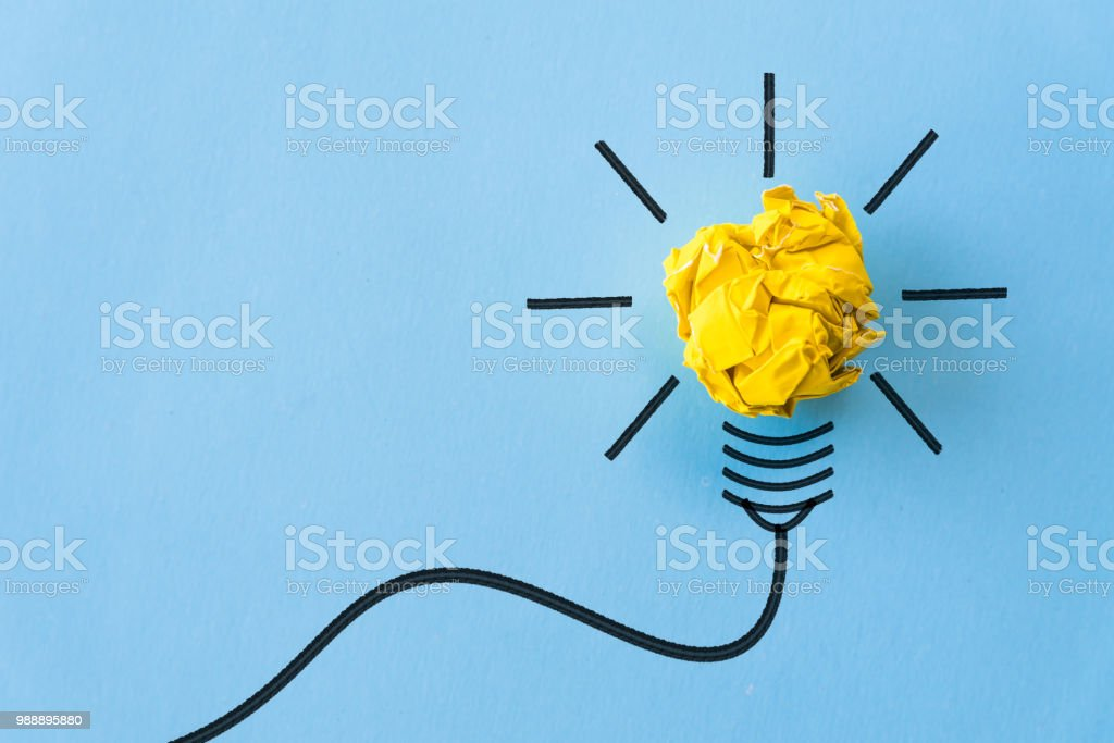 Inspiration and great idea concept. light bulb with crumpled yellow paper on blue background. royalty-free stock photo