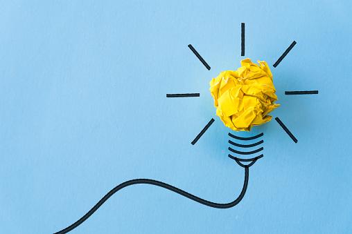 Inspiratie En Geweldig Idee Concept Lampje Met Verfrommeld Geel Papier Op Blauwe Achtergrond Stockfoto en meer beelden van Bedrijfsleven