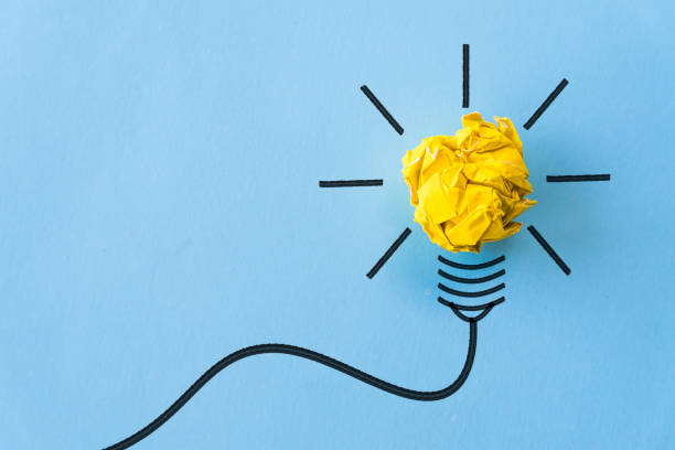 Inspiration and great idea concept. light bulb with crumpled yellow paper on blue background. - foto stock