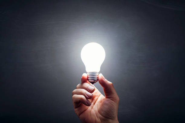 inspiration - light bulb hand idea blackboard - light bulb stock pictures, royalty-free photos & images