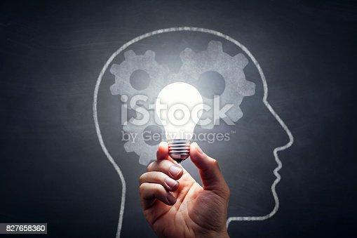 istock Inspiration - Light Bulb Hand Idea Blackboard 827658360