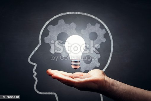 istock Inspiration - Light Bulb Hand Idea Blackboard 827658418