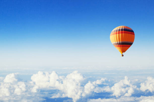 inspiration or travel background, hot air balloon over the clouds stock photo