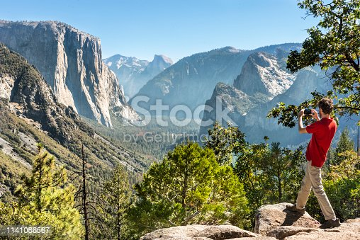 Man looking at view and photographing Yosemite valley with a smartphone. At Inspiration point, after Tunnel View