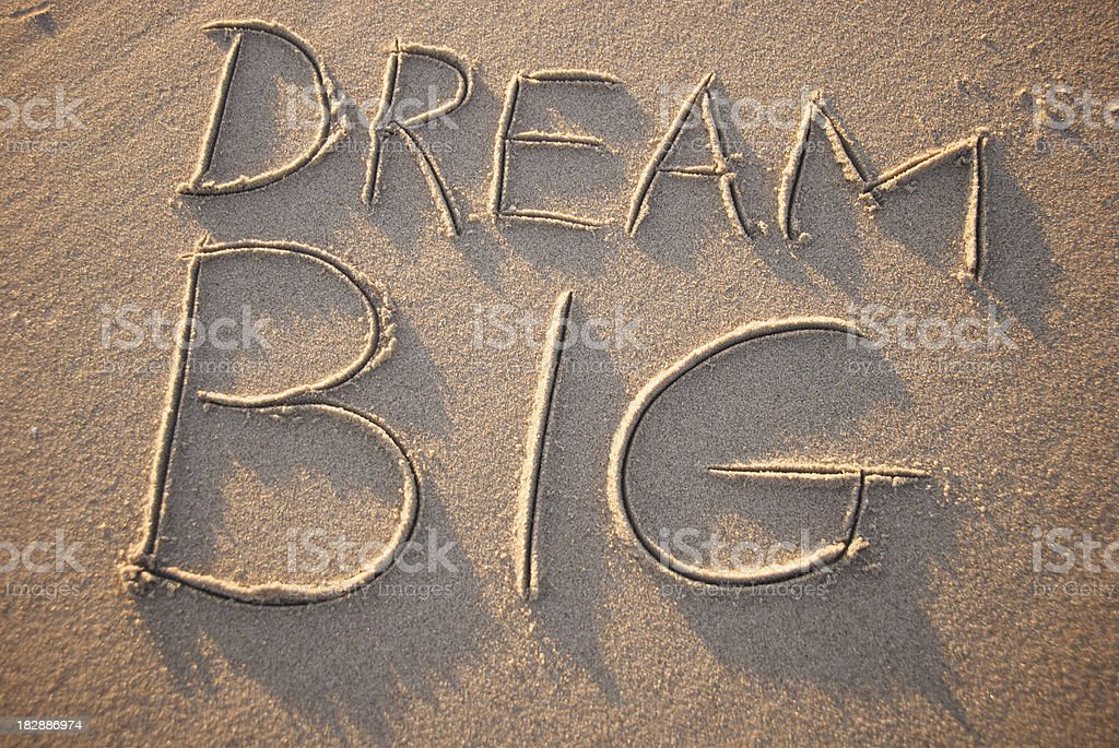 Inspirational dream big drawn in golden sand royalty-free stock photo