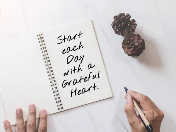 inspirierend, motivierend zitat auf notebook mit tannenzapfen und hände schrift auf weißem marmor-tisch hintergrund. - danke zitate stock-fotos und bilder