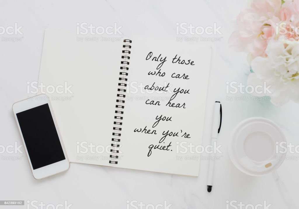 Inspirational motivating quote on notebook with smartphone, coffee cup and flower on white marble table background.