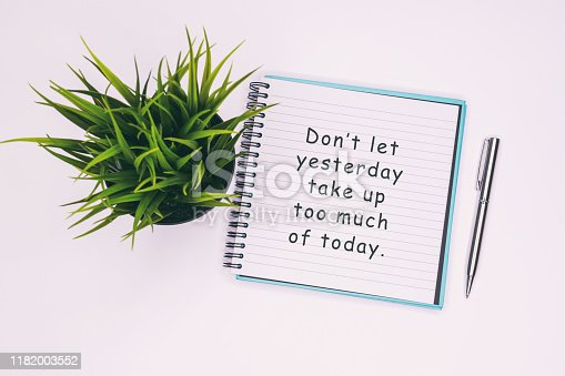 Don't let yesterday take up too much of today - Inspiration quotes on note pad.